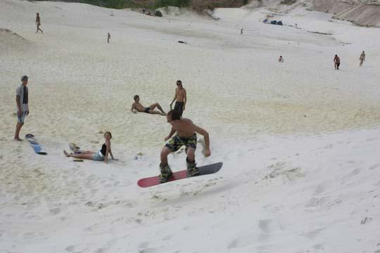Прыжок на сноуборде в песочном карьере